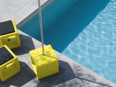 drie exemplaren van cube aan een zwembad, één gebruikt als parasolvoet, twee als pouf met een kussentje erop