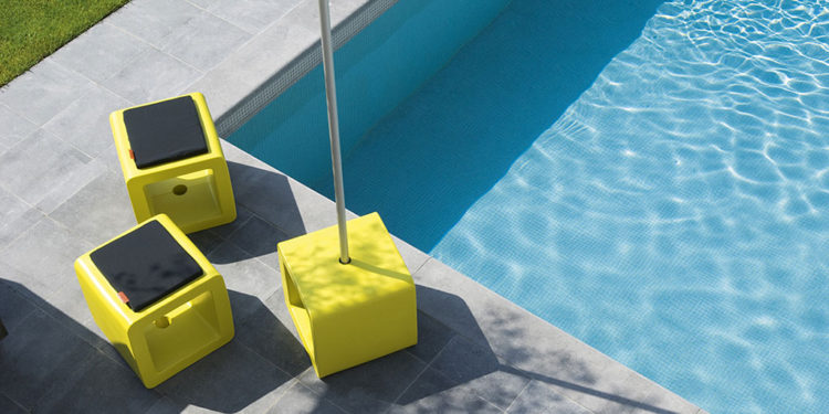 three cubes at a pool, one used as a parasol base, two as a pouf with a cushion on it